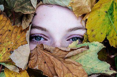 Augen einer Frau blicken aus einem Blätterberg heraus